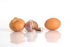 Ajo, cebolla y huevo aislados Imagen de archivo