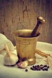Ajo, pimienta y un mortero de bronce Imagenes de archivo