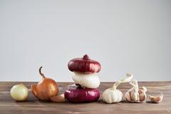 Ajo y cebolla frescos en fondo de madera Todavía vida con la verdura cruda Concepto de comida sana y de nutrición imágenes de archivo libres de regalías