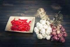 Ajo y cebollas rojas y chile en piso de madera oscuro Fotografía de archivo