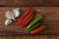 Ajo y chiles en un tablero de madera con las especias añadidas imagen de archivo libre de regalías