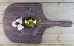 Ajo y Olive Oil en tablero rústico Imagenes de archivo