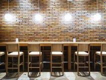 Ajournez la contre- barre avec des chaises et allumez le fond de mur de briques image stock