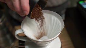 Ajoutant fraîchement le cafè moulu les haricots à l'versent au-dessus du dispositif d'écoulement de café avec le filtre de papier banque de vidéos