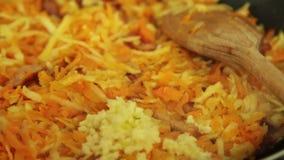 Ajoutant l'ail et rendant sous pour faire cuire le Bolonais de spaghetti dans la cuisine banque de vidéos