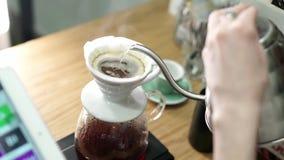Ajoutant l'eau chaude, le versant au café rôti pour le filtre banque de vidéos