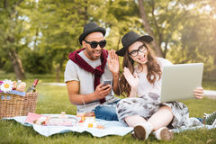 Ajouter à l'ordinateur portable écoutant la musique du smartphone en parc Images libres de droits