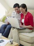 Ajouter à l'ordinateur portable et factures sur le sofa images libres de droits