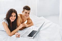 Ajouter à l'ordinateur portable sur le lit Photographie stock