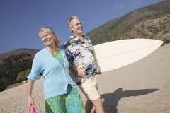 Ajouter à la planche de surf souriant sur la plage Image libre de droits