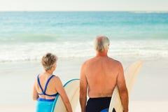 Ajouter à leur planche de surfing sur la plage Photos stock