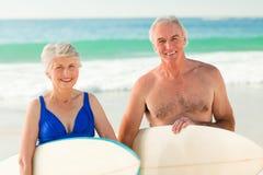Ajouter à leur planche de surfing sur la plage Image libre de droits