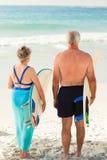 Ajouter à leur planche de surfing sur la plage Images libres de droits