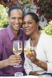Ajouter âgés par milieu aux verres de vin dehors Photo stock
