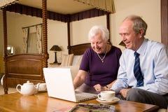 Ajouter aînés à l'ordinateur portatif dans la chambre à coucher d'hôtel Image stock