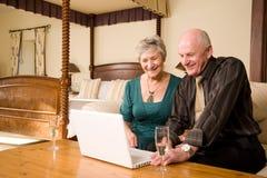 Ajouter aînés de sourire à l'ordinateur portatif Images stock