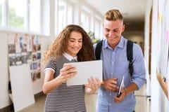 Ajouter adolescents d'étudiant au comprimé dans le lycée Images stock