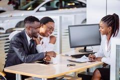 Ajouter africains heureux à la voiture de achat de revendeur dans le salon de l'Auto ou le salon Images libres de droits