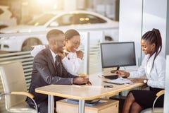 Ajouter africains heureux à la voiture de achat de revendeur dans le salon de l'Auto ou le salon Photo stock