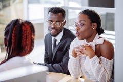 Ajouter africains heureux à la voiture de achat de revendeur dans le salon de l'Auto ou le salon Images stock