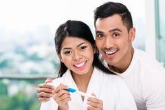 Ajouter asiatiques à l'essai de grossesse dans le lit Photos stock