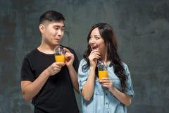 Ajouter assez asiatiques de jeunes aux verres de jus d'orange Images libres de droits