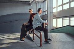 Ajouter attrayants de la jeunesse aux planches à roulettes se reposant sur un rail de morcellement dans le skatepark à l'intérieu photo stock