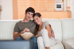 Ajouter au bol de maïs éclaté observant un film sur le sofa Photographie stock