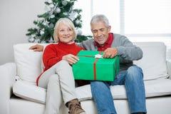 Ajouter au cadeau de Noël se reposant sur le sofa Images libres de droits
