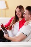 Ajouter au comprimé se reposant sur le divan à la maison Photos stock