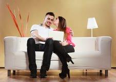 Ajouter au comprimé se reposant sur le divan à la maison Photos libres de droits