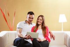 Ajouter au comprimé se reposant sur le divan à la maison Image libre de droits
