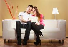 Ajouter au comprimé se reposant sur le divan à la maison Image stock