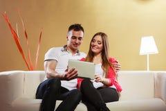 Ajouter au comprimé se reposant sur le divan à la maison Photo libre de droits
