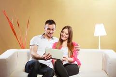 Ajouter au comprimé se reposant sur le divan à la maison Photographie stock libre de droits