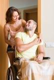 Ajouter au conjoint dans le fauteuil roulant près de la porte Images stock