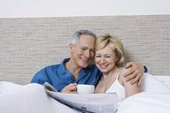 Ajouter au journal de lecture de tasse de café dans le lit Photographie stock libre de droits