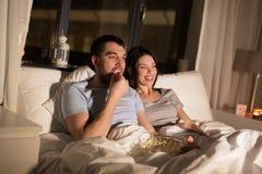 Ajouter au maïs éclaté regardant la TV la nuit à la maison Images stock