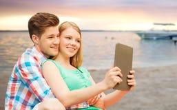 Ajouter au PC de comprimé prenant le selfie au-dessus de la plage Photos stock