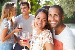 Ajouter aux amis buvant du vin et détendant dehors Photos stock