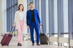 Ajouter aux bagages dans l'aéroport international Homme et femme allant sur l'atterrissage Photo libre de droits