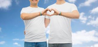 Ajouter aux bracelets et au coeur d'arc-en-ciel de fierté gaie Photos stock
