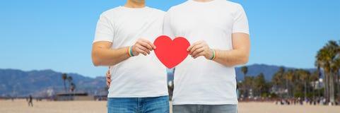 Ajouter aux bracelets et au coeur d'arc-en-ciel de fierté gaie Photo libre de droits