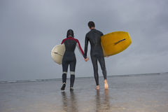 Ajouter aux planches de surf marchant vers la mer à la plage Photo libre de droits
