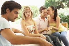 Ajouter aux problèmes parmi le groupe d'amis détendant sur le sofa Image libre de droits