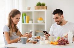 Ajouter aux smartphones prenant le petit déjeuner à la maison Images libres de droits