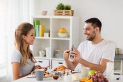 Ajouter aux smartphones prenant le petit déjeuner à la maison Photos stock