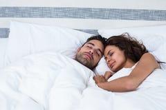 Ajouter aux yeux fermés tout en détendant sur le lit Photographie stock