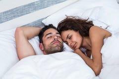 Ajouter aux yeux fermés tout en dormant sur le lit Photo libre de droits