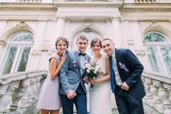 Ajouter de nouveaux mariés au garçon d'honneur heureux plus la demoiselle d'honneur posant aux escaliers du bâtiment classique image stock